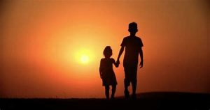 two children holding hands at sunrise