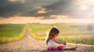child sitting on road by field
