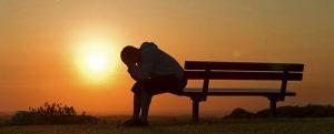 depressed man at sunset on bench