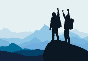 two people standing on top of mountain with arms raised