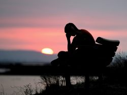 man with head down on bench at sunset